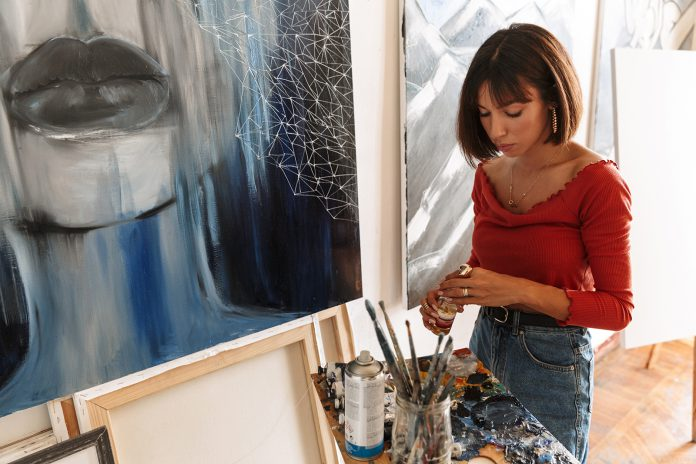 Portrait of young woman using painting tools while drawing in st