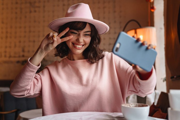 Happy positive woman using mobile phone take a selfie.