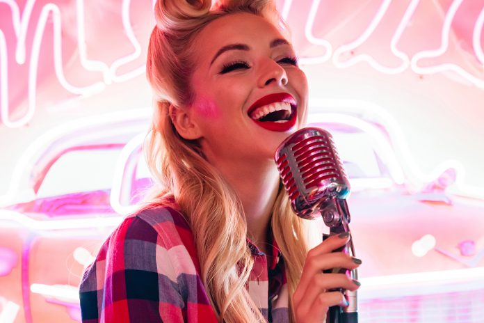 Photo of cheerful caucasian woman with microphone singing and sm