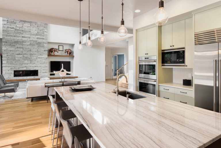 Urban Kitchen with Granite Tops, Exposed Bulb Lights and Island